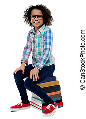 School girl sitting on stack of books