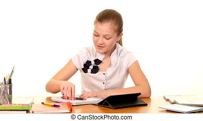 School girl sitting, thinking and writing homework in workbook using a book on white background