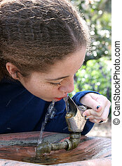 School Girl Takes A Drink - A school girl taking a drink of...