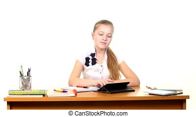 School girl taught lessons using the tablet computer doing homework on white background