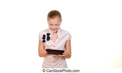 School girl using tablet computer and becomes happy finding something, on white background, slow motion