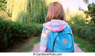 Rear view of school girl with backpack walking along park alley