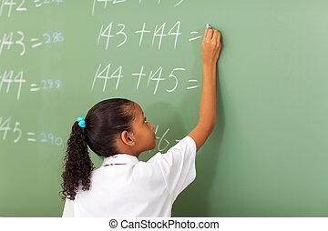 school girl writing maths answer - primary school girl...