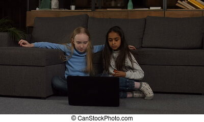 School girls studying on line with laptop at home