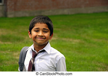 A happy Indian school kid smiling in front of the classroom