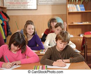 School lesson - Six schoolchildren are writing during lesson...