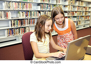 Two cute school girls doing research online in the school library.