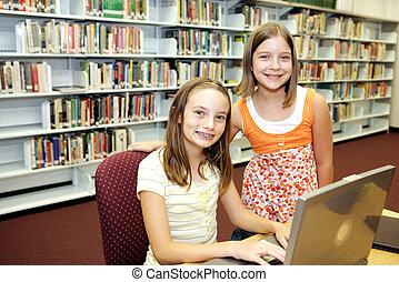 School Library - Technology in Class - Two cute school girls...