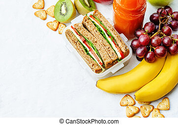 school lunch with a sandwich, fresh fruits, crackers and...