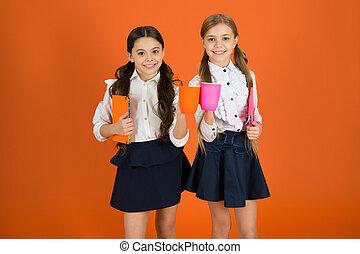 School mates relaxing with drink. Enjoy being pupil. Girls kids school uniform orange background. Schoolgirl hold book or notepad and mug. School routine. Having break relax. Drinking tea while break