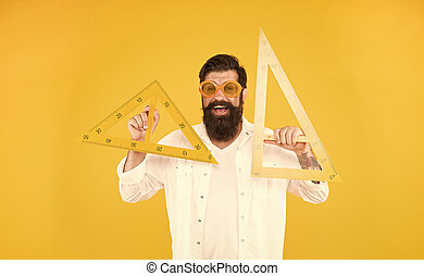School of engineering. Happy engineer or designer. Smart engineer holding triangles on yellow background. Teaching engineer smiling with drawing instruments ready for working. Architectural engineer