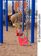 A vertical shot of school or park playground equipment with flexible swings