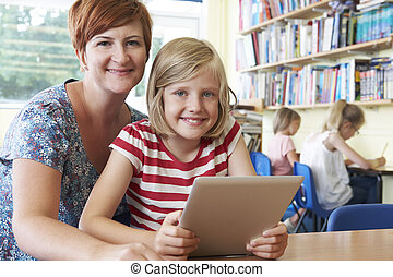 School Pupil With Teacher Using Digital Tablet Computer In Class