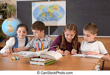 School routine - Four schoolchildren aged 11 at the desk in...