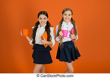 School routine. Having break relax. Drinking tea while break. School mates relaxing with drink. Enjoy being pupil. Girls kids school uniform orange background. Schoolgirl hold book or notepad and mug