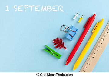 School stationery on a blue background. Inscription September 1. Knowledge day concept. Copy space