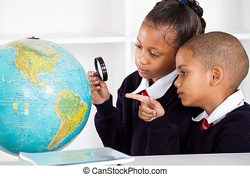 school students looking at globe - two elementary school...