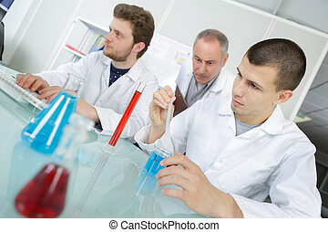 school students with teacher in chemistry class