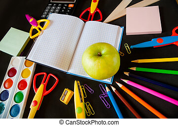 school supplies and a large green apple on  notepad in the center