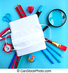 School supplies and medical mask on blue background, top view. Back to school concept