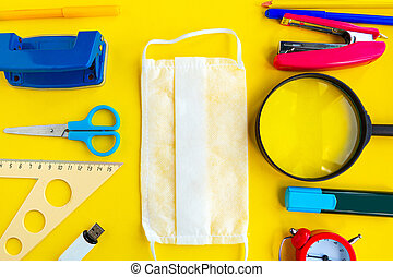 School supplies and medical mask on bright yellow background, top view. Back to school concept
