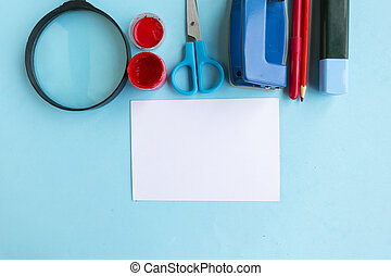School supplies and white mockup blank on blue background, top view. Back to school concept
