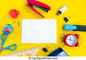 School supplies and white mockup blank on bright yellow background, top view. Back to school concept