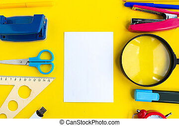 School supplies and white mockup blank on yellow background, top view. Back to school concept