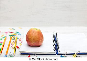 School supplies, notebook, apple on  white wooden background