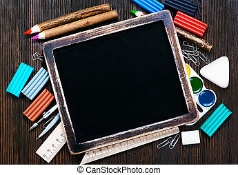 school supplies on a table, black board and school supplies