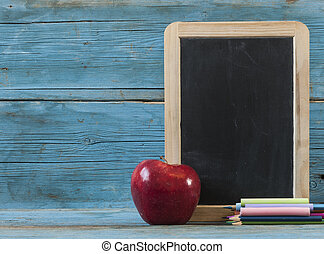 School supplies on blackboard  and empty surface.