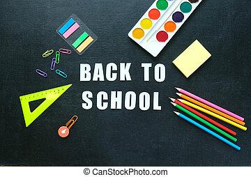 School supplies on blackboard background. Back to school concept