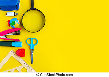 School supplies on bright yellow background, top view. Back to school concept. Copy space for the text