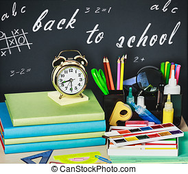 school supplies on the desk in the background of chalkboard