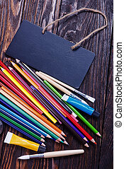 school supplies on the wooden table, black board and school supplies