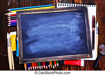 school supplies on the wooden table, black board and school...