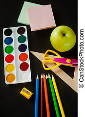 school supplies - paint, pencils, scissors, a ruler and  big green apple