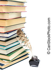 school supplies. quill in the inkwell and a large stack of different books on a white background close-up.