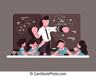 School teacher at lesson. Teaching children in classroom....
