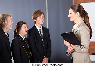 school teacher talking to students - happy high school...