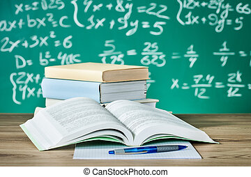 School textbooks on a desk in front of blackboard