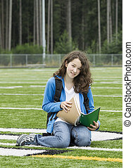 School Time Again - Young girl studying on soccer field with...