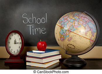 a chalkboard with the words school time written on it, a clock, books, apple, chalk and a globe sit on a teachers desk.