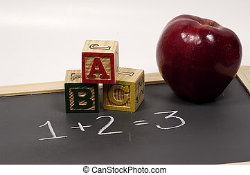 Photo of Chalkboard, Blocks and Apple. Classroom Objects.