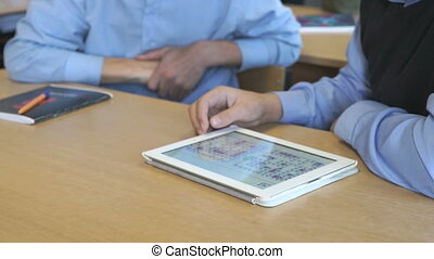 Schoolboy aged 14s plays the game using a tablet - Schoolboy...