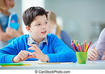 Schoolboy at lesson - Portrait of cute schoolboy sitting at...