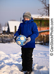 Schoolboy boy kicks the ball playing in winter football on the snow cover.