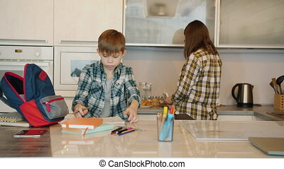 Schoolboy is doing homework writing in notebook while caring mother is cooking food in kitchen. Modern education and family life concept.
