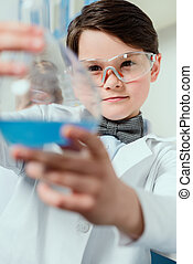 schoolboy in goggles holding flask in chemical lab, science student concept
