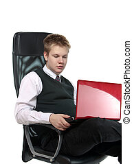 schoolboy in office armchair, with the laptop